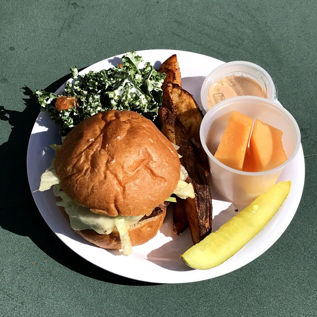 A lunch plate at New London, CT schools that includes a whole grain-rich Chabaso bread bun alongside kale, sweet potato fries, pickle and cantaloupe.